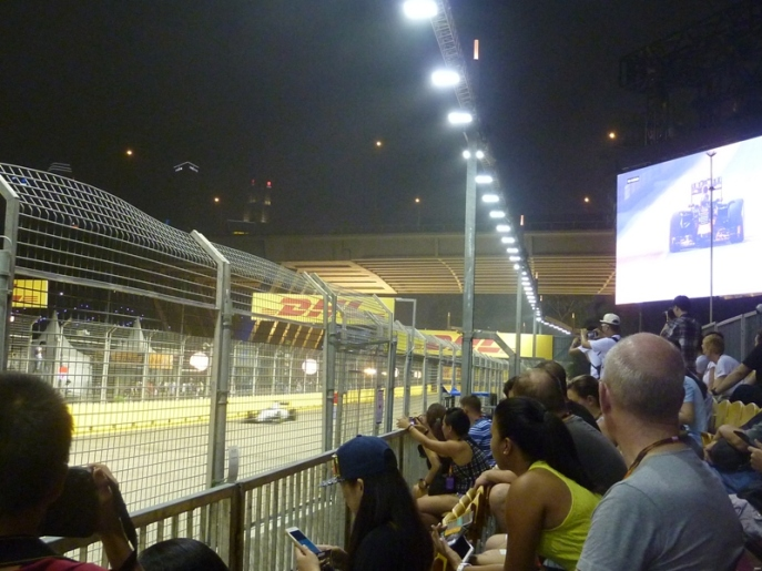 FP2 from the viewing platform with free seating reserved for Premier Walkabout Ticket holders opposite the T21 straight, with a widescreen TV.